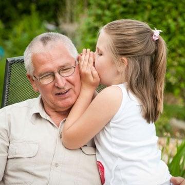 A little girl whispering in her grandpa's ear