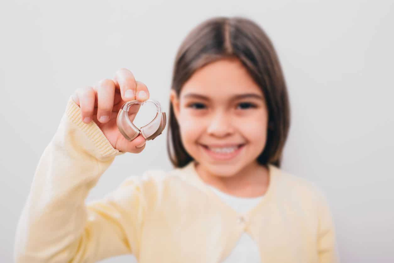 Girl Holding Hearing Aids