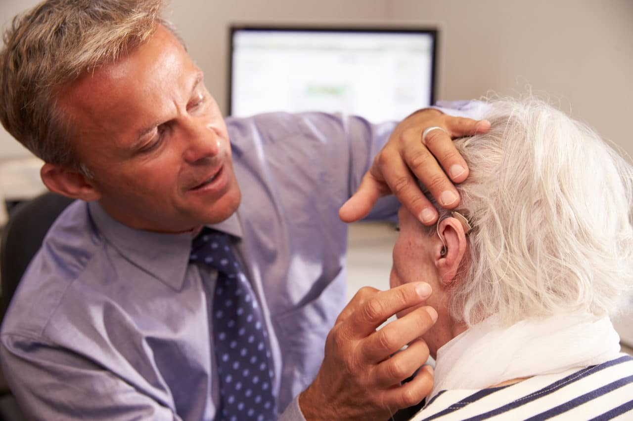 audiologist fitting a man with a hearing aid