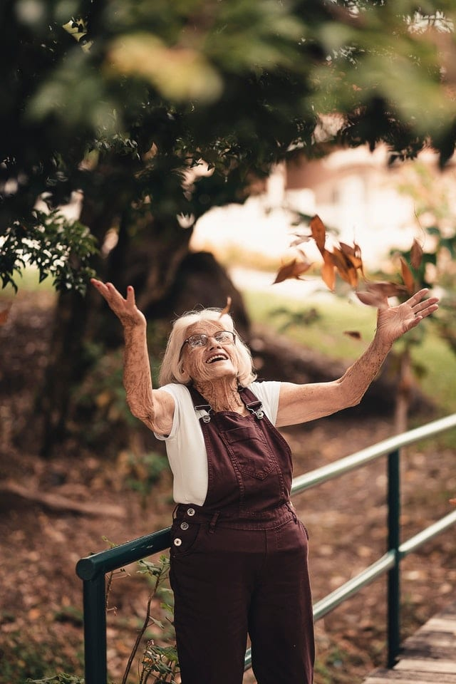 Woman throwing leaves into the air looking happy