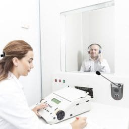 female audiologist testing a patient's hearing while male patient sits in booth