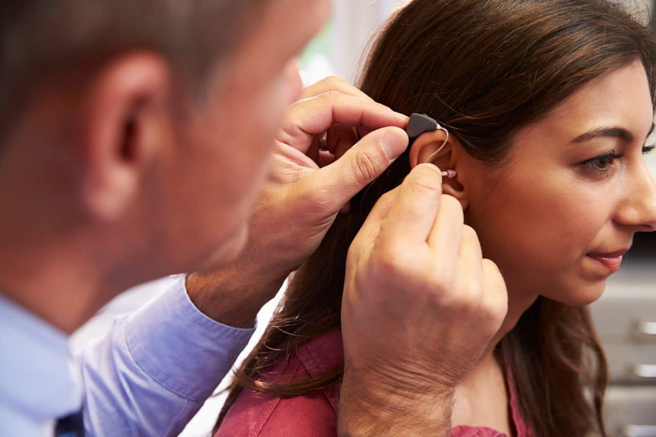 Woman gets fitted for hearing aid.