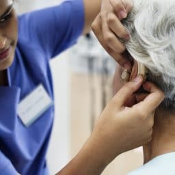 Woman being fitted with a hearing aid.