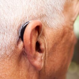 Man's ear with a very modern, low-profile and discrete hearing aid.